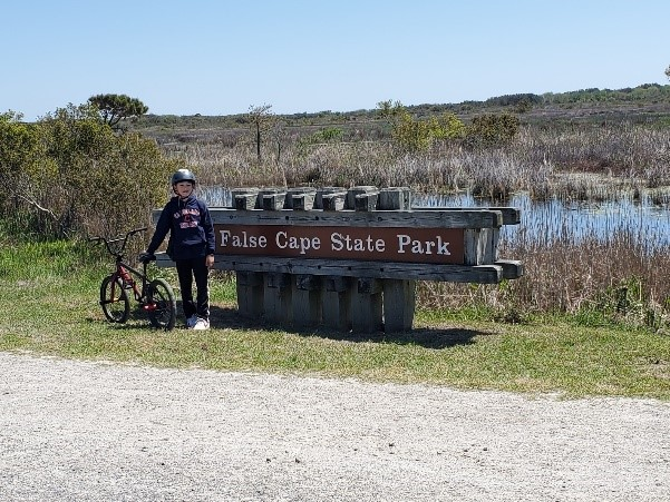 False Cape State Park sign with a young bike rider